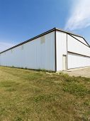 Plain large aluminum building in rural setting.