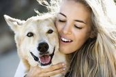 Pretty Caucasian blond woman hugging brown dog and smiling.