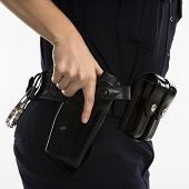 Close up side view of mid adult female Caucasian law enforcement officer hand on gun in holster.