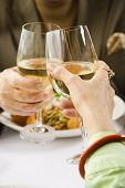 Caucasian mature couple toasting with white wine in restaurant.