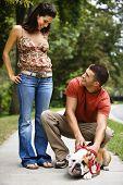 Caucasian mid adult couple with English Bulldog on sidewalk.