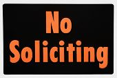 No soliciting sign with orange text against black.