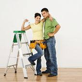 Couple with tools and ladder standing in home smiling.
