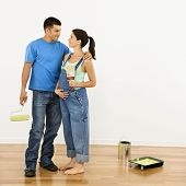 Pregnant woman and husband preparing to paint interior home wall.