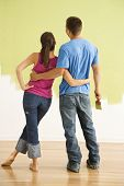 Attractive couple standing in front of partially painted wall with arms around each other.