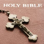 Crucifix lying on cover of closed Holy Bible.