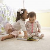 Caucasian girl children sitting on bedroom floor looking at book. [3.5 years old and 8 months old]