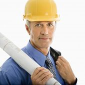 Caucasian middle aged businessman holding blueprints and wearing hard hat.