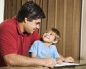 Hispanic father and   son doing homework and making eye contact.
