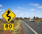 Van on asphalt two lane road in rural Australia with speed limit and curve ahead road sign.