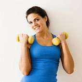 Woman holding hand weights and smiling.
