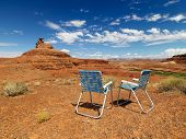 Two lawn chairs in scenic desert landscape with  land formation.