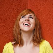 Portrait of smiling and laughing redhead looking up.