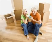 Middle-aged couple sitting on floor among cardboard moving boxes with coffee.