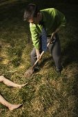 Young businessman uses a shovel to bury a womans body out in a field. Vertical shot.