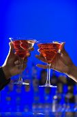 African-American hands toast martini glasses against a bright blue background. Vertical shot.