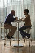 An African-American man and woman enjoy each other's company over a cup of coffee.  They are seated at a small cafe table on stools. Vertical shot.