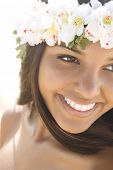 Attractive young Hawaiian woman with a lei on her head smiling. Vertical shot.