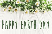 Happy Earth Day Text Sign On Beautiful Daisy Flowers On Rustic White Wooden Background Top View. Gre poster