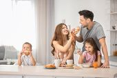 Happy family having breakfast in kitchen poster