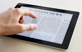 picture of perception  - Man hands are pointing on touch screen device with business news - JPG
