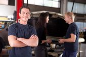 Portrait of a mechanic looking at the camera with a customer and second mechanic in the background