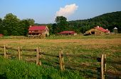 stock photo of split rail fence  - Rustic farm id comlete with house barn out buildings and split rail fence - JPG