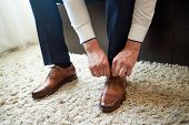 Businessman Tying Shoe Laces Indoors, Close Up. Man Dressing Up With Elegant Leather Shoes. Groom Pr poster