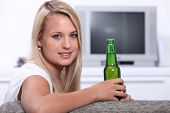 image of underage  - Young woman at home with a bottle of unopened lager - JPG