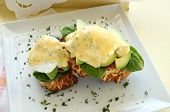 stock photo of benediction  - Beautiful eggs benedict with bacon and a rich hollandaise sauce on tiger crust bread - JPG