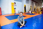 Happy Little Boy Sitting On Trampoline Among Group Of Kids Indoors poster