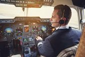 Side View Serene Pilot Talking By Headset While Situating In Cabin With Appliances. Appliance Concep poster