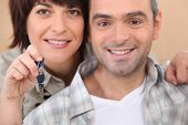 Mature couple holding up a set of keys