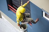Painters Hanging On Roll, Painting Color On Building Wall. Young Painting Facade Builder Worker With poster