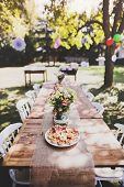 Table Set For A Garden Party Or Celebration Outside. Flowers And Snacks On The Decorated Table In Th poster