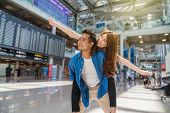 Happiness Asian Couple Traveler At The Flight Information Screen In Moddern An Airport, Lifestyle Tr poster