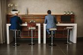 Rear View Shot Of Two Businessmen Sitting At Free Internet Service Counter In Airport Lounge. Busine poster