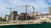 Site Buildings Under Construction And Cranes. High-rise Building Under Construction. The Site With C poster