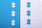 White Details Of A Puzzle On Blue Background. A Puzzle Is A Puzzle From Small Pieces. Heart Shape Of poster