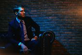 Respectable handsome man in elegant suit sitting in apartments with classical luxurious interior. Me poster