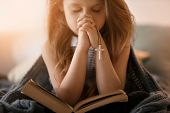 Religious Christian girl praying over Bible indoors poster