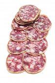 una pila de salchichón, salami español, sobre un fondo blanco