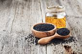 Black cumin oil with seeds on wooden background poster