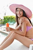 Swimsuit Concept. Beautiful Girl In Swimsuit Is Applying Sunscreen. Beautiful Girl In A Swimsuit Pro poster