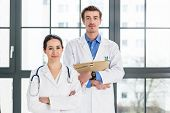 Portrait of two determined physicians wearing white medical gowns while looking at camera with serio poster