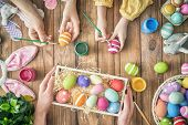 A mother, father and their child painting eggs. Happy family preparing for Easter. poster