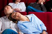 Couple and other people, probably friends, in cinema watching a movie, it seems to be a boring movie