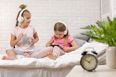Two Cute Children Girls Playing In The Bedroom. Two Cute Children Girls Use Digital Tablet In Bed. poster