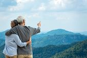 Asian Lifestyle Senior Couple Hug And Pointing The Mountain Nature.  Old People Happy In Love Romant poster