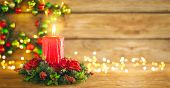Burning Christmas red candle and  festive Christmas arrangement on a wooden table. Christmas advent poster